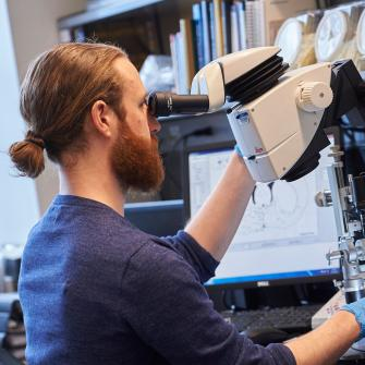 Neuroscience Institute Trainee Examines a Microscopic Sample
