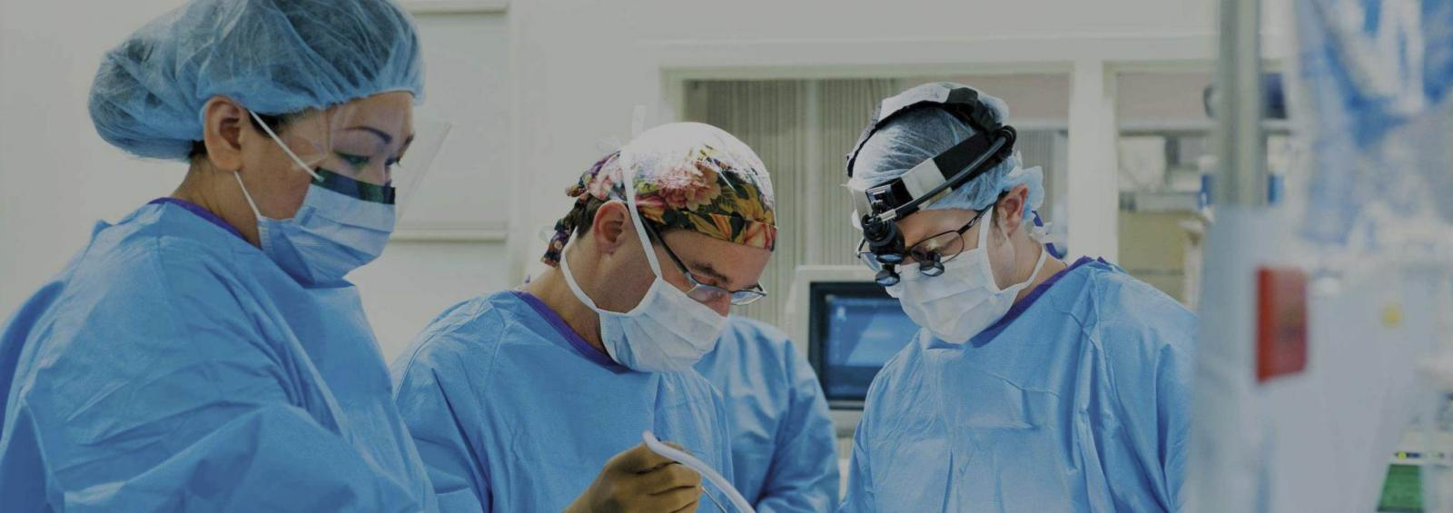 Three Surgeons Perform Procedure in Operating Room