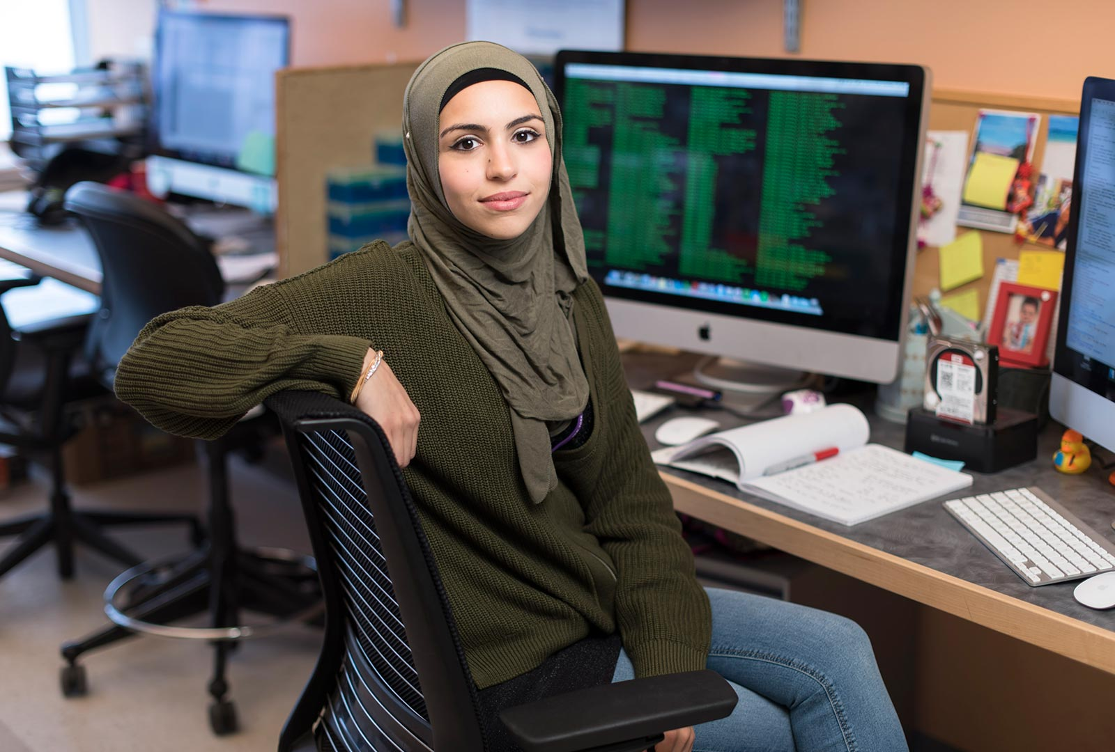 PhD Candidate Sana Badri Sitting in Front of Computer