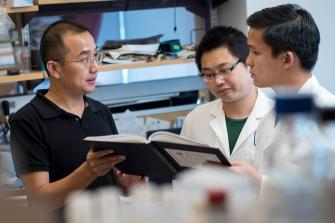 Dr. Lei Bu Speaks with Researchers in Lab