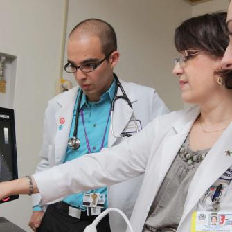 Physician and Students Examine Diagram on Computer