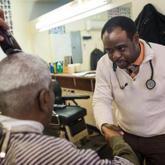 Dr. Joseph Ravenell Shakes Man's Hand in Barbershop